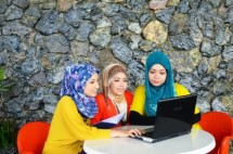 Stock Photo of Three People Looking at a Laptop