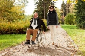 Stock Photo of a Wheelchair User and Companion in a Park