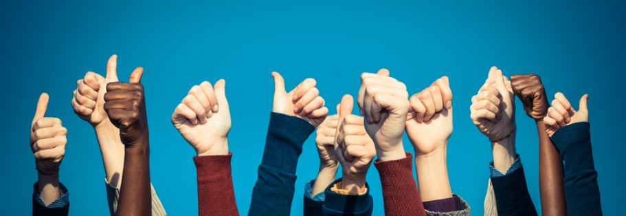 Stock Photo of Hands Giving a Thumbs Up in the Air