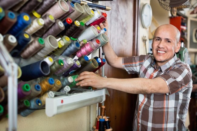Man smiling in sewing shop