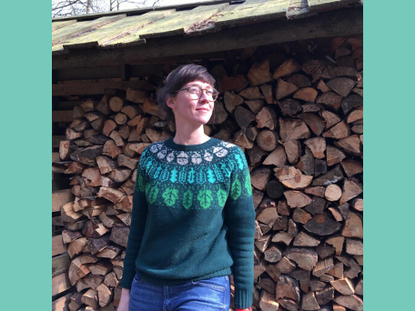 A woman standing in front of logs of wood