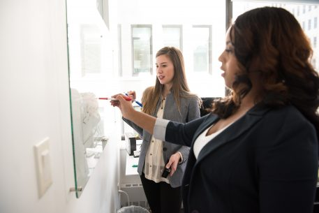 Two women writing on a whiteboard